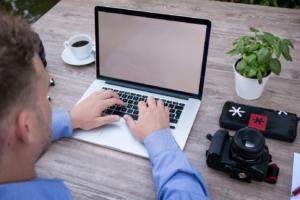 Mann mit Laptop an Schreibtisch mit Pflanze